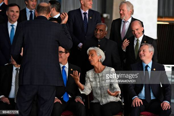 IMF Managing Director Christine Lagarde gestures next to French Economy Minister Bruno Le Maire as they prepare to pose for the family picture during...