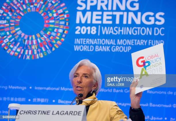 IMF Managing Director Christine Lagarde holds up a copy of the Global Policy Agenda as she holds a press conference during the 2018 Spring Meetings...
