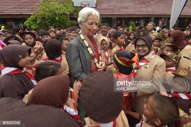 Managing Director of the International Monetary Fund Christine Lagarde greets schoolchildren during a visit in Cilincing Jakarta on February 28 2018...