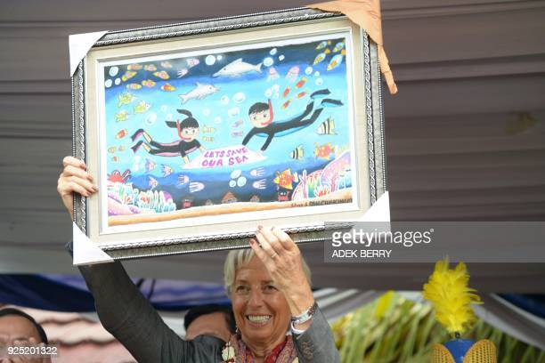 Managing Director of the International Monetary Fund Christine Lagarde holds a drawing during a visit in Cilincing Jakarta on February 28 2018...