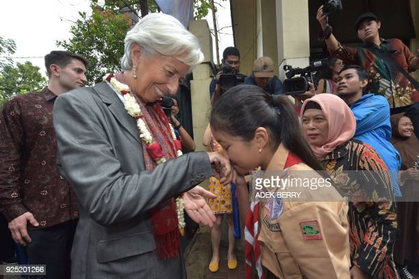 Managing Director of the International Monetary Fund Christine Lagarde is greeted by an Indonesian schoolgirl during a visit in Cilincing Jakarta on...