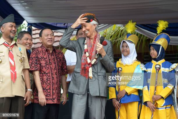 Managing Director of the International Monetary Fund Christine Lagarde wears a Javanese traditional cap during a visit in Cilincing Jakarta on...