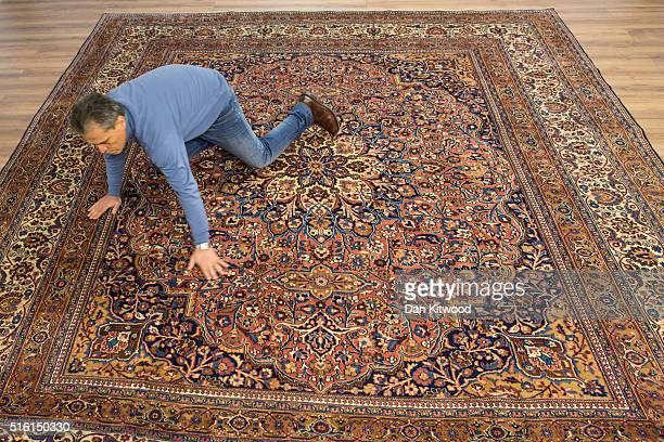 Managing director of the Oriental Rug Centre Jalil Ahwazian flattens out an antique 'Dorokhsh' Persian Rug in the Oriental Rug Centre's main...
