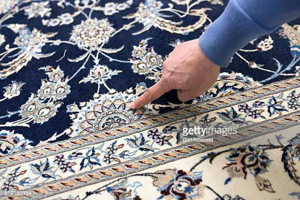 Managing director of the Oriental Rug Centre Jalil Ahwazian points to details on a 'Nain' Persian Rug in the Oriental Rug Centre's main warehouse on...