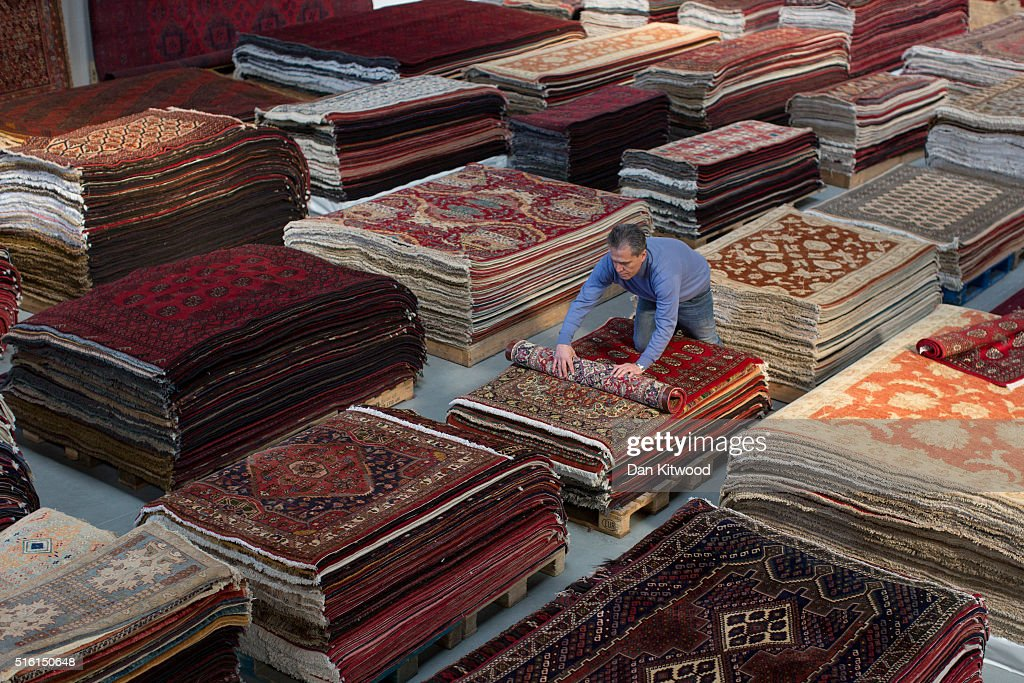 Managing Director Of The Oriental Rug Centre, Jalil Ahwazian Rolls A  Persian Rug At The