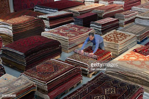 Managing director of the Oriental Rug Centre Jalil Ahwazian rolls a Persian rug at the Oriental Rug Centre's main warehouse on March 17 2016 in...