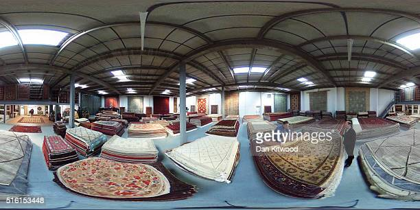 Managing director of the Oriental Rug Centre Jalil Ahwazian rolls a Persian 'Bidjar' rug in the Oriental Rug Centre's main warehouse on March 17 2016...