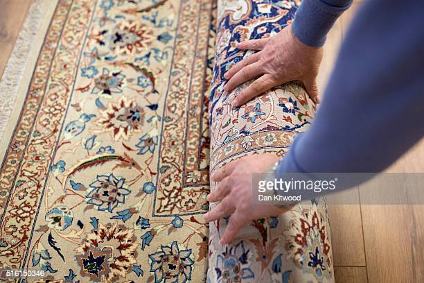Managing director of the Oriental Rug Centre Jalil Ahwazian rolls up a 'Nain' Persian Rug in the Oriental Rug Centre's main warehouse on March 17...