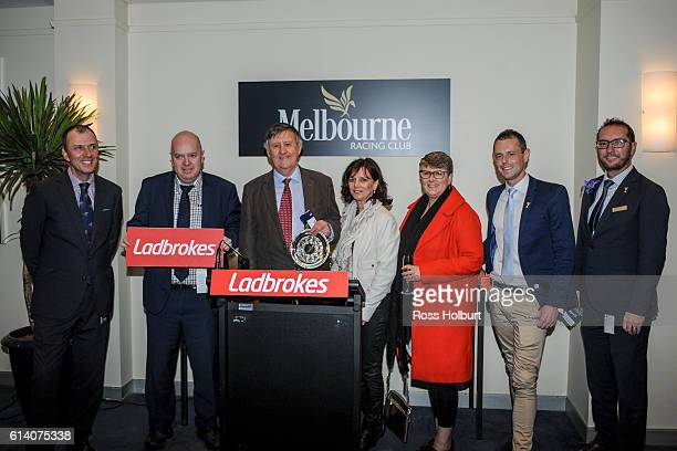Managing owner John Clark holds the trophy with connections after Ferro Nero won Ladbrokes Handicap at Caulfield Racecourse on October 12 2016 in...