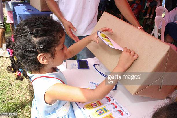 A girl casts her vote in the special general election for children 29 October 2006 in Managua Nicaragua The ballot have the same candidates for the...