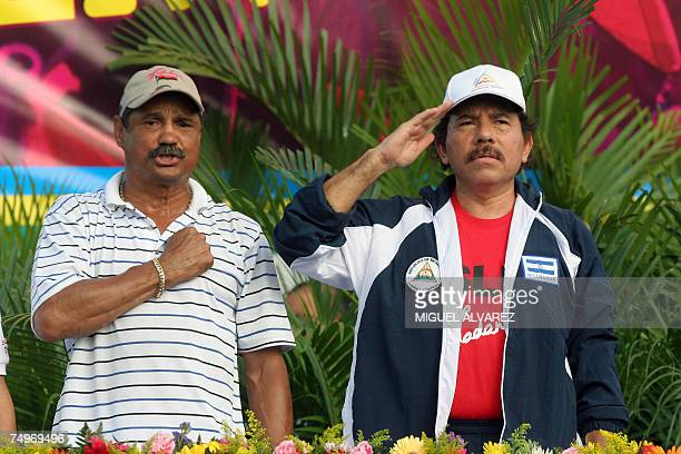 Nicaragua's President Daniel Ortega and former box world champion and deputy mayor of Managua Alexis Arguello sing the national anthem 30 June 2007...