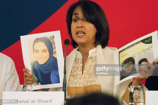 Manal alSharif a Saudi Arabian activist who started the #women2drive movement and was arrested for driving while female holds up photos of Saudi...