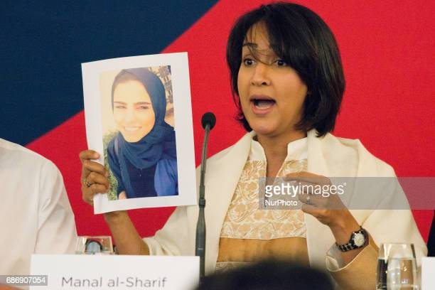 Manal alSharif a Saudi Arabian activist who started the #women2drive movement and was arrested for driving while female holds up a photo of Saudi...