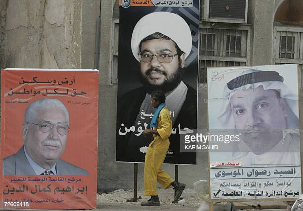 A Bahraini man walks past billboards carrying photos and slogans of legislative candidates Jassim alMumin Radwan alMusawi and Ibrahim Kamal alDein in...