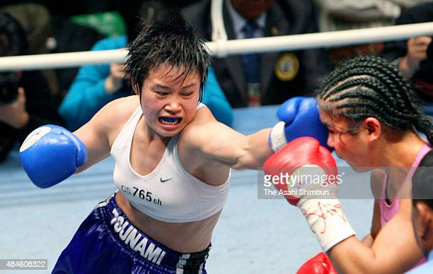 Manami Arima whose ring name is Tsunami Tenkai of Japan punches her left on Zhang Xiyan of China during their WBA Women's Super Flyweight title bout...