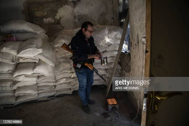 Manarmed with a Kalashnikov assault rifle makes coffee inside a shelter of a village in Nagorno-Karabakh on October 23 during the ongoing fighting...