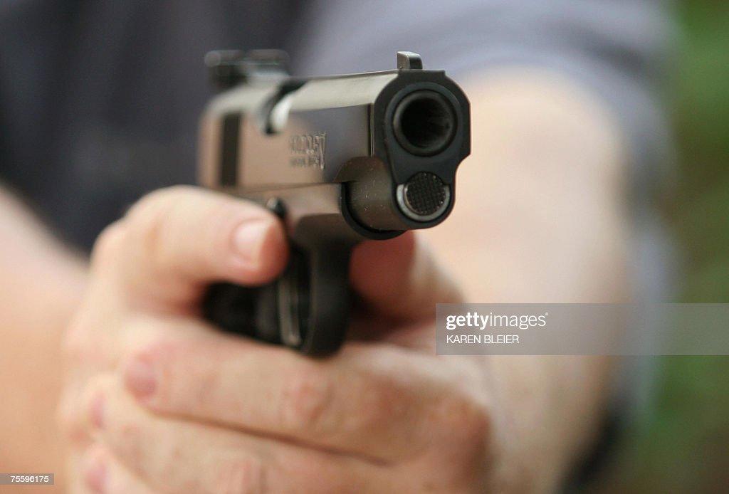 An unidentified man holds a Colt .45 sem... : News Photo