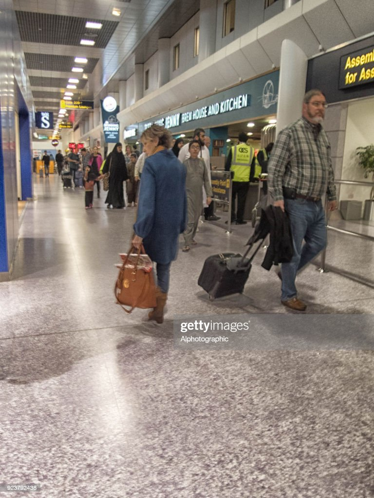 Manchester Airport Shops With Passengers Walking Past Stock