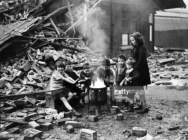Manchester children warm themselves by the brasier following an air raid on the city March 1941 P004579