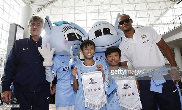 Manchester City Assistant coach Brain Kidd posses for a photo with the Manchester City mascots Hong Kong fans Edison Lai Andrew Lo and team captain...
