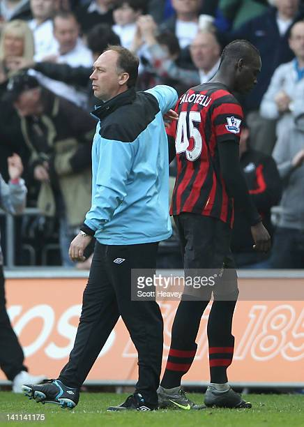 Manchester City assistant manager David Platt pats Mario Balotelli on the back after defeat in the Barclays Premier League match between Swansea City...