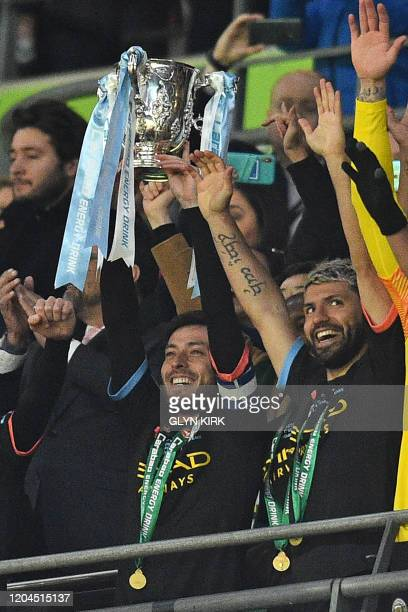 Manchester City captain David Silva lifts the trophy as his teammates celebrate their win after the English League Cup final football match between...