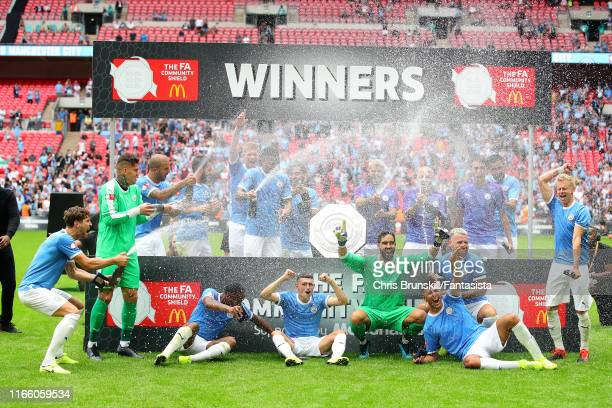 Manchester City celebrate with the trophy following the FA Community Shield match between Liverpool and Manchester City at Wembley Stadium on August...