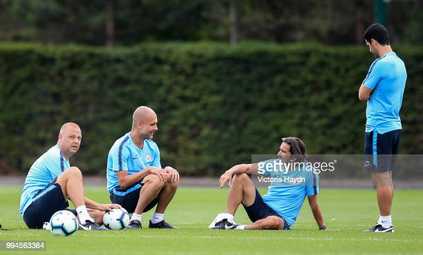 Manchester City coaches Rodolfo Borrell Pep Guardiola Lorenzo Gonzalez and Mikel Arteta relax during training at Manchester City Football Academy on...