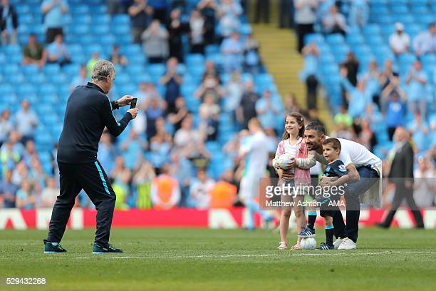 Manchester City coAssistant Manager Brian Kidd takes pictures of Aleksandar Kolarov and his children after the Barclays Premier League match between...