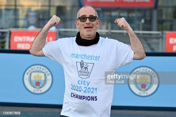 Manchester City fan celebrates his club winning the Premier League title, outside the Etihad Stadium in Manchester, north west England, on May 11...