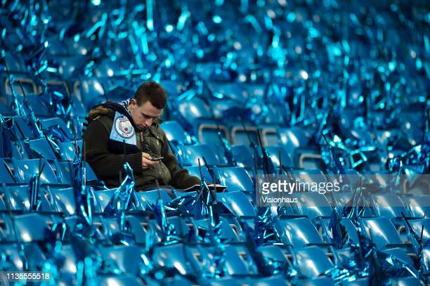 Manchester City fan checks his phone while waiting for kick off before the UEFA Champions League Round of 16 Second Leg match between Manchester City...
