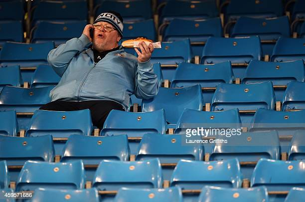 Manchester City fan enjoys a bite to eat prior to kickoff during the UEFA Champions League Group E match between Manchester City and FC Bayern...