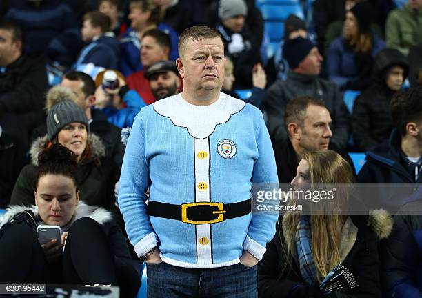 Manchester City fan gets in the christmas spirit with a christmas jumper prior to kick off during the Premier League match between Manchester City...