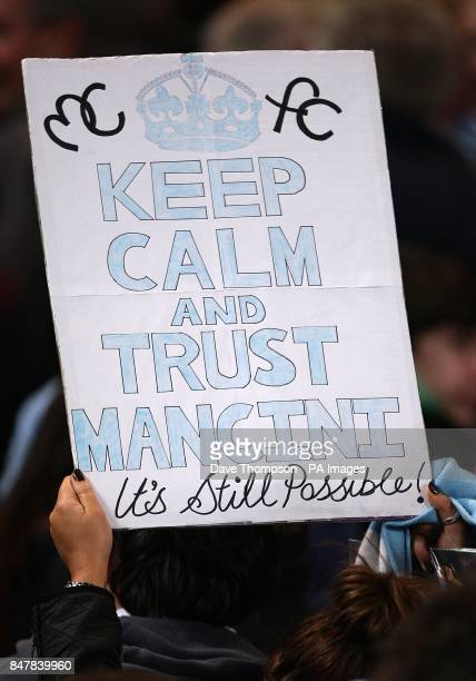 A Manchester City fan holds banner up in the stands syaing Keep Calm and Trust Mancini It's Still Possible