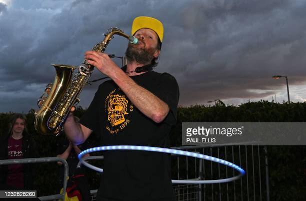 Manchester City fan plays a Saxophone as he celebrates their club winning the Premier League title, outside the Etihad Stadium in Manchester, north...