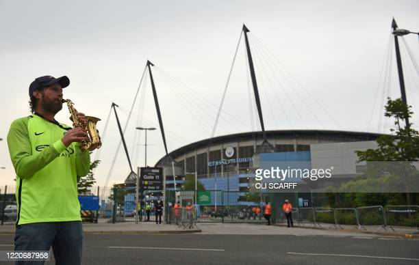 A Manchester City fan plays a saxophone as waits outside the Etihad Stadium where the English Premier League football match between Manchester City...