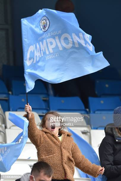 Manchester City fan waves a flag in the stands ahead of the English Premier League football match between Manchester City and Everton at the Etihad...