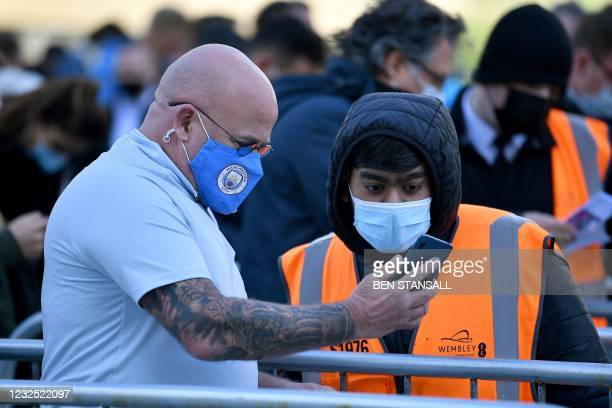 Manchester City fan wearing a face covering shows a worker his phone as he arrives at Wembley Stadium to watch the English League Cup final football...