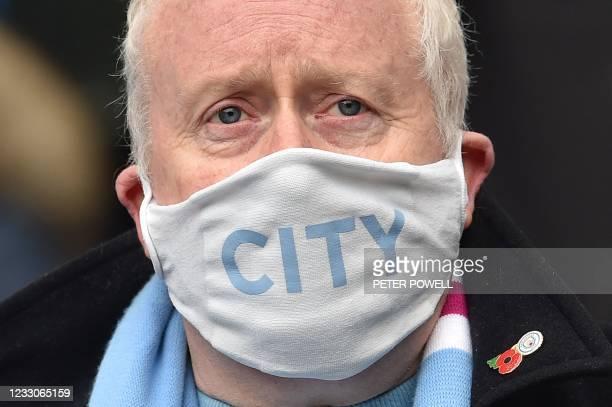 Manchester City fan wears a face mask as a precaution against the novel coronavirus during the English Premier League football match between...