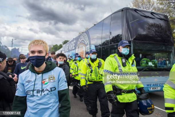 Manchester City fan wears a 'Free Palestine' sticker on his shirt as police officers escort the team bus to the Premier League match between...