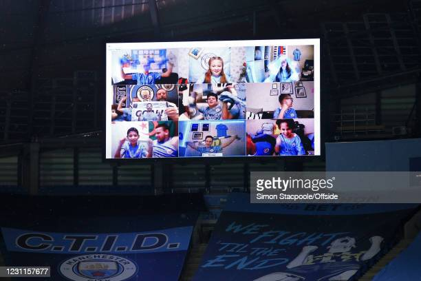 Manchester City fans are displayed on the big screen celebrating their team's 3rd goal during the Premier League match between Manchester City and...