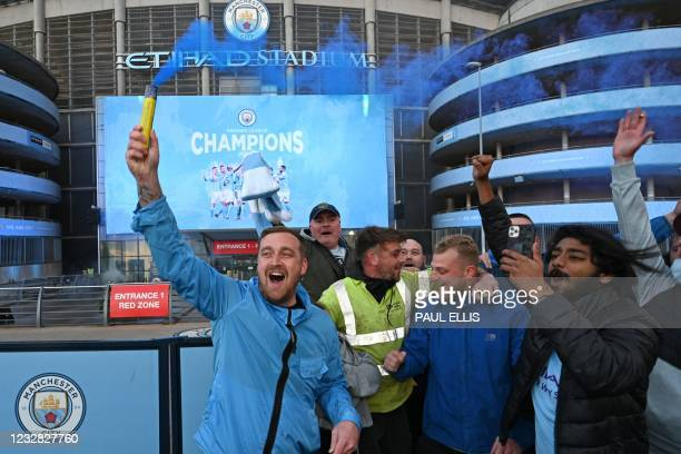 Manchester City fans celebrate their club winning the Premier League title, outside the Etihad Stadium in Manchester, north west England, on May 11...