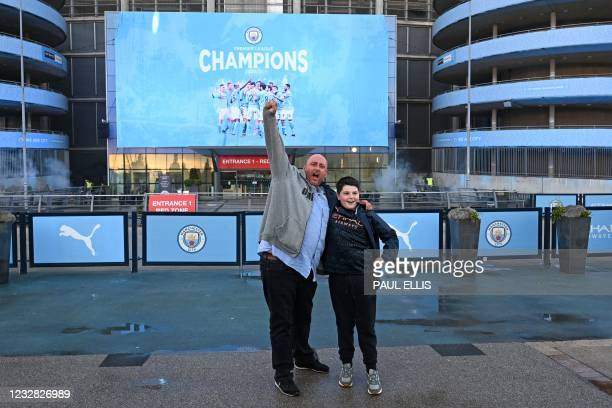 Manchester City fans celebrate winning the Premier League title outside the Etihad Stadium in Manchester, north west England, on May 11 after their...