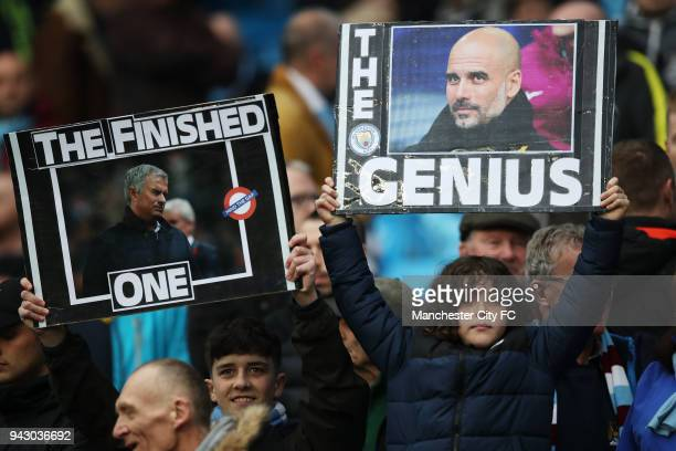 Manchester City fans hold up signs supporting their manager prior to the Premier League match between Manchester City and Manchester United at Etihad...