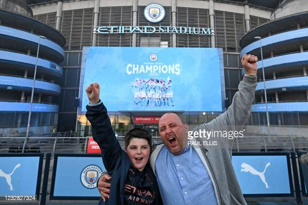 Manchester City fans, Ian Leonard and his son Jack celebrate winning the Premier League title outside the Etihad Stadium in Manchester, north west...