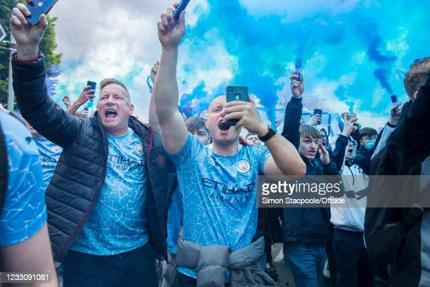 Manchester City fans let off blue flares before the Premier League match between Manchester City and Everton at Etihad Stadium on May 23, 2021 in...