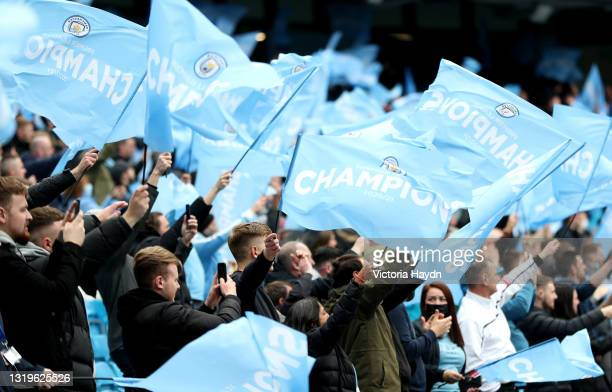 Manchester City fans show their support as they wave 'champions' flags prior to the Premier League match between Manchester City and Everton at...