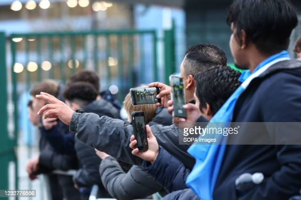 Manchester City fans take photos as the team buses depart at Etihad Stadium. Fans had gathered in anticipation of winning the Premier League title,...