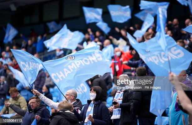 Manchester City fans wave champions flags during the Premier League match at the Etihad Stadium, Manchester. Picture date: Sunday May 23, 2021.