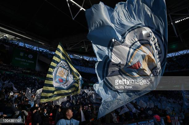 Manchester City fans wave flags ahead of the English League Cup final football match between Aston Villa and Manchester City at Wembley stadium in...